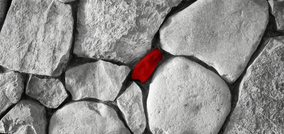 Ein roter Stein in Mitte von Gruppe verschiedener Steine von oben